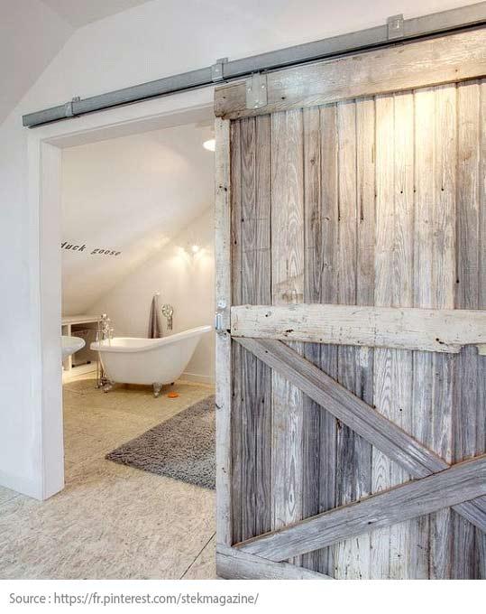 Une porte de grange qui donne sur la salle de bain